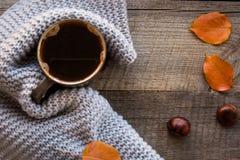 在木板的温暖的围巾包裹的咖啡 顶视图,葡萄酒样式,静物画 免版税库存图片