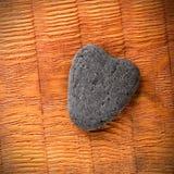 在木板的灰色石心脏 免版税库存图片