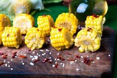 在木板的烤玉米切片有盐和红色的烘干了胡椒 关闭 免版税库存图片