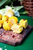 在木板的烤玉米切片有盐和红色的烘干了胡椒 关闭 库存图片