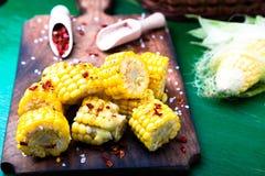 在木板的烤玉米切片有盐和红色的烘干了胡椒 关闭 库存照片