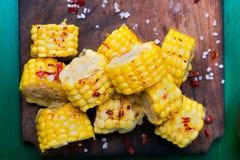 在木板的烤玉米切片有盐和红色的烘干了胡椒 顶视图 库存图片