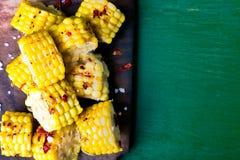 在木板的烤玉米切片有盐和红色的烘干了胡椒 顶视图 库存照片