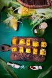 在木板的烤玉米切片有盐和红色的烘干了胡椒 顶视图 图库摄影