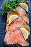 在木板的熏制鲑鱼有dil和柠檬的 图库摄影