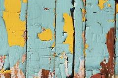 在木板的破裂的老油漆 绿松石和黄色 免版税库存照片