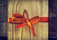 在木板的红色丝绸丝带弓当拷贝空间 免版税库存照片