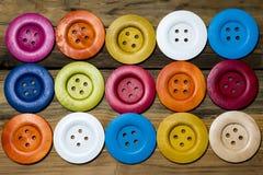 在木板的色的按钮,五颜六色的按钮,在老木 免版税库存图片