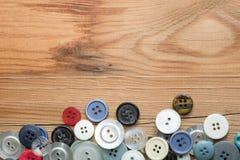 在木板的色的按钮,五颜六色的按钮 免版税图库摄影