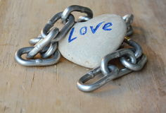 在木板的链卷心脏石头 免版税库存图片
