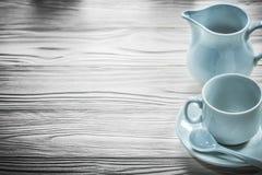 在木板的陶瓷杯子茶碟茶匙盛奶油小壶 免版税库存照片