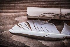 在木板的滚动的葡萄酒纸羽毛 免版税库存照片