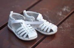 在木板走道的儿童的凉鞋 免版税库存图片