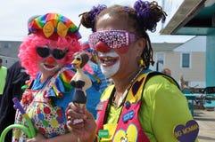 在木板走道的小丑游行 库存图片