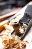 在木板,有刨花的木匠业工具的老飞机 库存照片