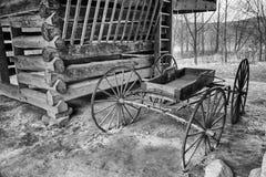 在木构架的日志谷仓停放的古色古香的无盖货车 图库摄影