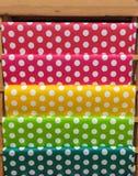 在木架子的五颜六色的经典红色,桃红色,黄色,绿色和蓝色圆点样式纸DIY工作的 免版税库存照片