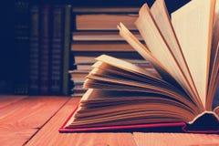在木架子的图书馆里打开的书 与拷贝空间的教育背景文本的 被定调子的照片 免版税库存照片