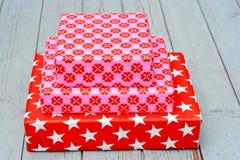 在木架子背景的红色和桃红色星花纹花样圣诞节礼物 库存照片