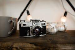 在木架子背景的老影片照相机在斯堪的纳维亚样式的顶楼内部 轻的火光 库存照片