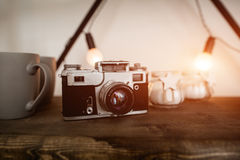 在木架子背景的老影片照相机在斯堪的纳维亚样式的顶楼内部 轻的火光 免版税库存照片