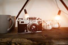 在木架子背景的老影片照相机在斯堪的纳维亚样式的顶楼内部 轻的火光 免版税库存图片