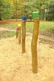 在木柱子的钢单杠对于儿童操场 在酒吧下的橙色沙子,绿色公园 免版税库存照片
