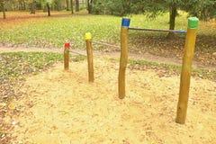 在木柱子的钢单杠对于儿童操场 在酒吧下的橙色沙子,绿色公园 库存照片