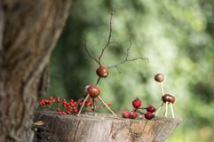 在木树桩的栗子动物,鹿和母鹿由栗子、橡子和枝杈,与秋天红色fru的绿色背景制成 库存照片