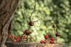 在木树桩的栗子动物,鹿和母鹿由栗子、橡子和枝杈,绿色背景制成用秋天果子 免版税库存照片