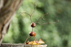 在木树桩的栗子动物,鹿由栗子制成,橡子和枝杈,绿色背景 图库摄影