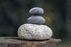 在木树桩,白色和灰色凝思小卵石的三块禅宗石头堆耸立 免版税图库摄影
