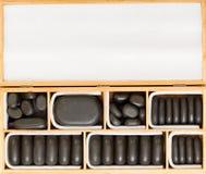 在木案件的黑温泉禅宗按摩石头删去拷贝空间 免版税库存照片