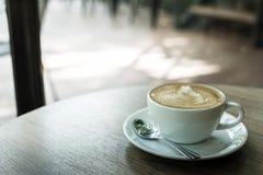 在木桌、葡萄酒和减速火箭的styl上的热的拿铁艺术咖啡杯 免版税库存图片