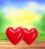 在木桌、被弄脏的自然背景和gr上的两红色心脏 免版税库存照片