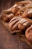 在木桌、麦子、麦子的纸袋、耳朵,绳索和粗麻布上的新鲜的黑麦面包 垂直的照片 库存图片