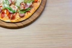 在木桌上供食的可口意大利薄饼 库存照片