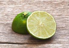 在木桌上切开的柠檬石灰 库存图片