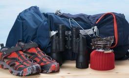 在木桌上和蓝色背景、旅客集合、大蓝色背包、鞋子、双筒望远镜和煤气喷燃器 免版税库存照片