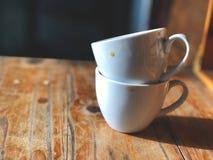 在木桌上堆积的两个加奶咖啡杯子与早晨点燃 图库摄影