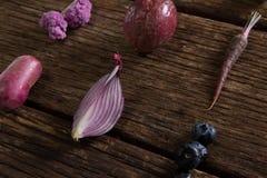 在木桌上安排的各种各样的菜 免版税图库摄影