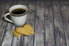 在木桌上是一个白色杯子,一个残破的谷物曲奇饼 库存图片