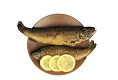 在木桌上是有两条被烘烤的鱼的一块板材 免版税库存照片