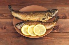 在木桌上是有两条被烘烤的鱼鳟鱼的一块板材 免版税库存照片