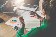 在木桌上是纸图、智能手机、笔记本和膝上型计算机 坐在桌和谈话上的两个女商人 库存照片