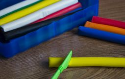 在木桌上有用彩色塑泥不同的片断的一个蓝色框,在它旁边是多彩多姿的彩色塑泥和plasti 库存图片