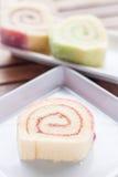 在木桌上服务的五颜六色的果酱卷 免版税库存照片