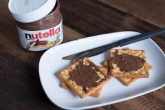 在木桌上涂的Nutella巧克力 库存照片