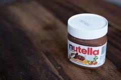 在木桌上涂的Nutella巧克力 免版税库存图片