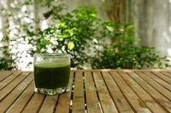 在木桌上的一块绿色汁液玻璃在庭院里 免版税库存照片